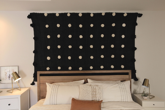 Image of the bed and hanging tapestry used as a headboard