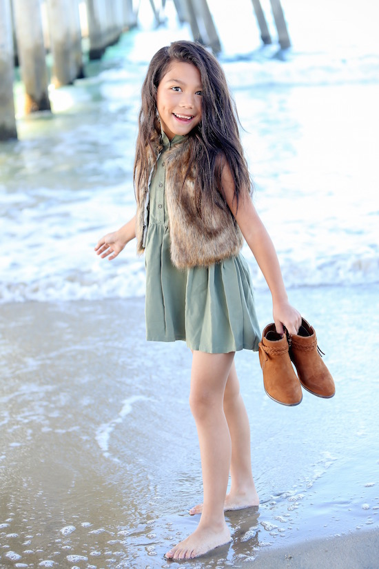 Txunamy wearing a dress, faux fur vest and boots