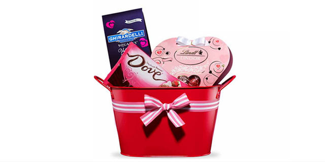 A red basket with a pink bow and Valentine's Day candy inside.