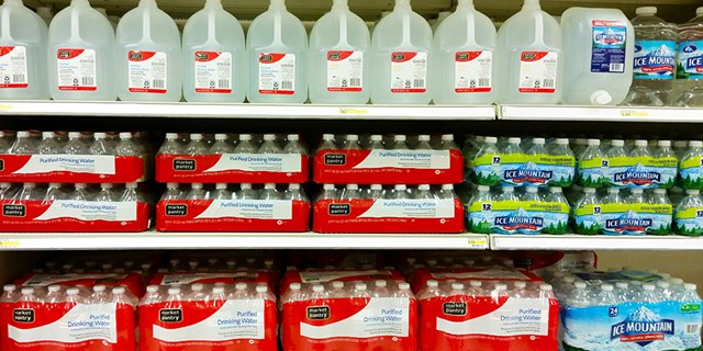 A Target shelf filled with bottles and jugs of water.