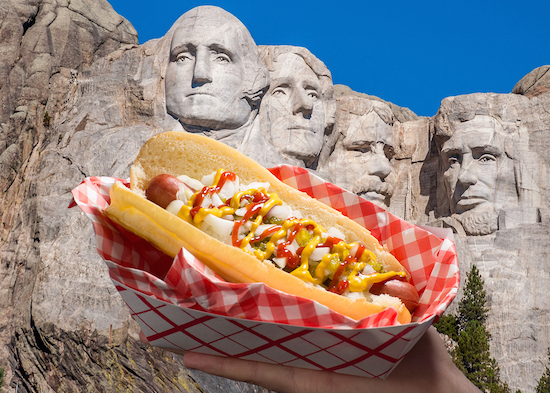 Hot dog topped with onions, pickle relish and ketchup and mustard in front of a photo of Mount Rushmore