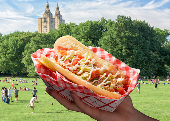 Hand holding up a hot dog topped with BLT toppings in front of a Central Park background