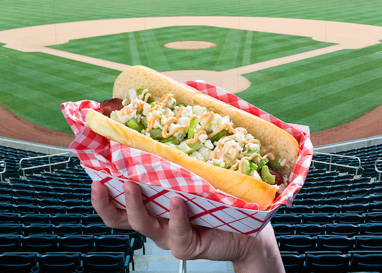 Picture of a hand holding up a buffalo sauce blue cheese hot dog in front of an empty baseball field