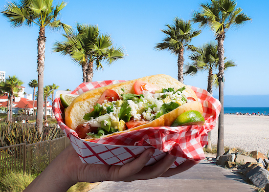 Picture of a hot dog topped with avocado, tomatoes, onions, jalapeno slices and more in front of a California background