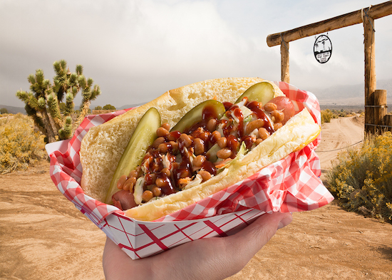 Picture of a hot dog topped with baked beans, barbecue sauce and pickle spears in front of a western ranch background