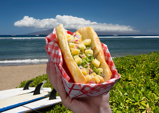 Hot dog topped with pineapple, snap peas, red onion and teriyaki sauce in front of a Hawaiian ocean background