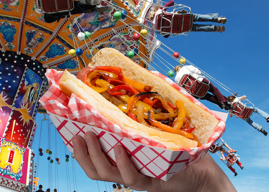 Picture of a hot dog topped with peppers and onions in front of a carnival ride background