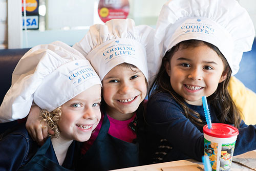 Three kids in chef hats smile and drink smoothies