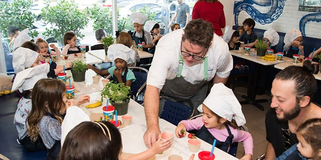 Chef Jamie DeRosa helps a group of kids make strawberry smoothies at tables in his restaurant