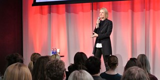 Elizabeth Gilbert stands onstage speaking in front of the audience