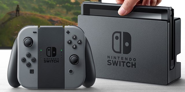 The Nintendo Switch gaming system in gray in front of a screen