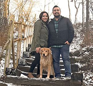 Dominic Smith and his wife and their dog, standing on snowy steps