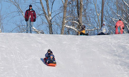Parents and kids sledding on a hill