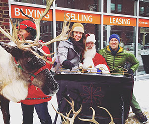 Rebecca Molloy and her husband with santa and a reindeer at a Christmas Market