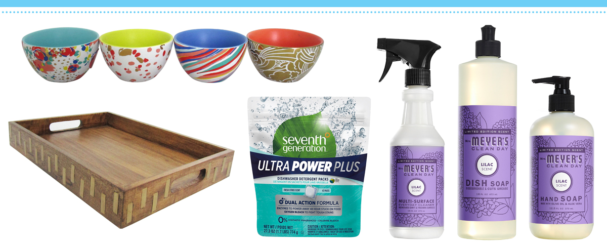 Colorful bowls, a wooden tray, a package of dishwasher pods, and bottles of soap and cleaning spray