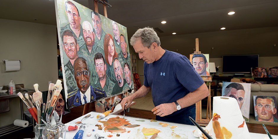 President George W. Bush stands at his easel in his studio painting portraits of veterans