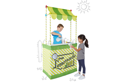 Two kids pour lemonade with their lemonade stand kit.