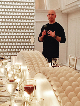 Todd Waterbury speaks into a microphone, surrounded by a beautiful display of white eggs.