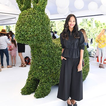 Zoe Saldana stands next to a bunny-shaped topiary
