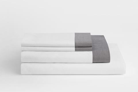 A stack of folded white sheets with grey edging is shown against a light background