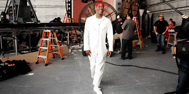 Lil Yachty, dressed in white, behind-the-scenes at a video shoot.
