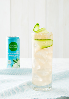 A cocktail garnished with a cucumber slice alongside a blue can of cucumber mint sparkling water