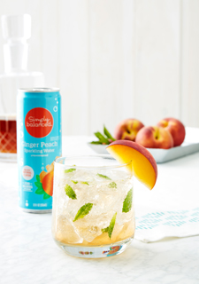 A cocktail garnished with a peach slice and mint sprigs, alongside a blue can of ginger peach sparkling water