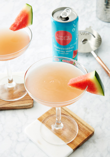 A cocktail garnished with a watermelon slice alongside a blue can of watermelon sparkling water
