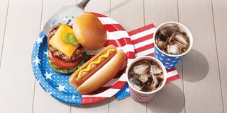 A grilled burger, hot dog and two cups of soda with patriotic paperware