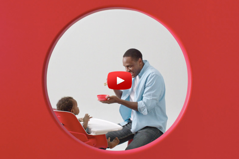 A dad feeds a child sitting in a red high chair