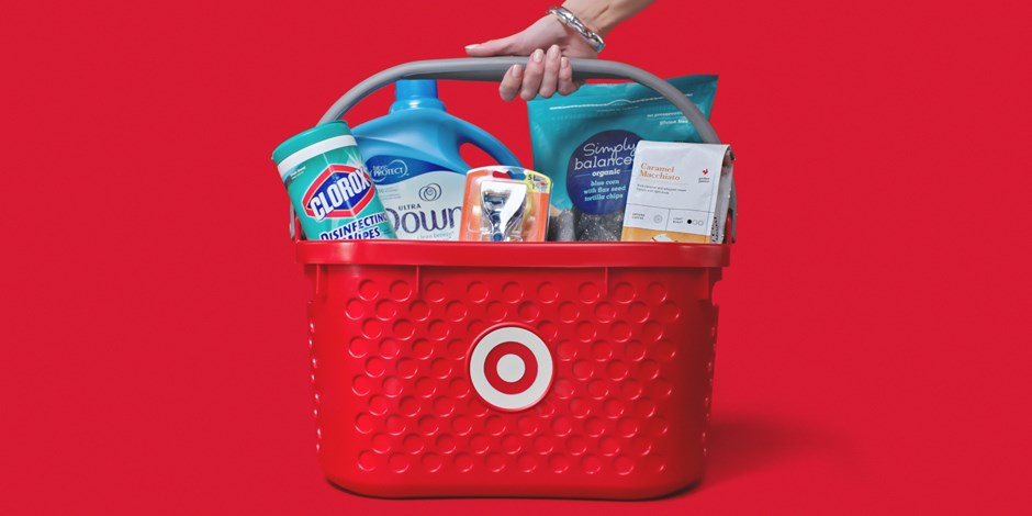 A hand grabs a red Target basket, full of wipes, a razor, coffee, fabric soften and chips.