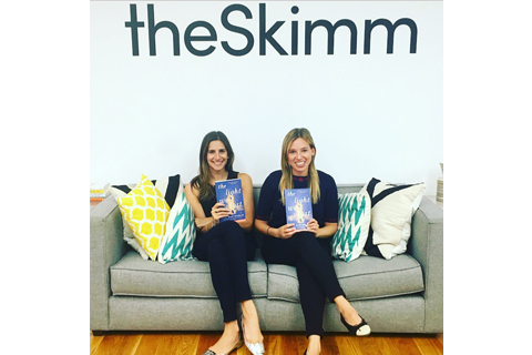 "Carly Zakin and Danielle Weisberg sit on a couch holding copies of ""The Light We Lost"" with ""theSkimm"" on the wall above"