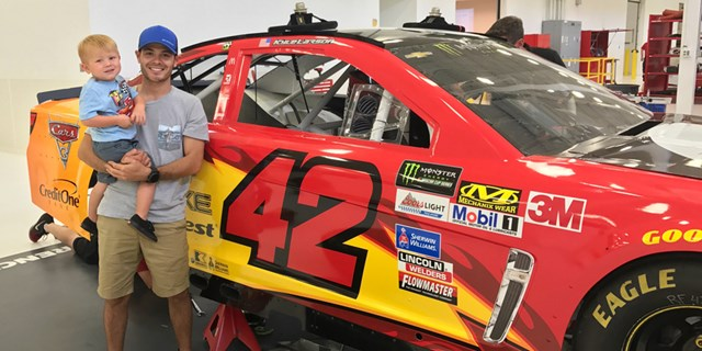 Kyle Larson and son Owen smile in front of his Lightning McQueen-inspired car