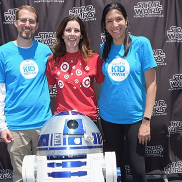 Three volunteers take a photo with R2-D2.
