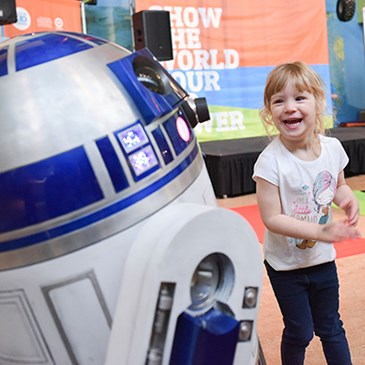 A little girl smiles as she meets R2-D2