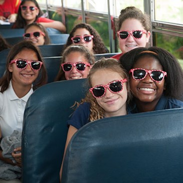 Kids on a bus smile for the camera in their Target sunglasses