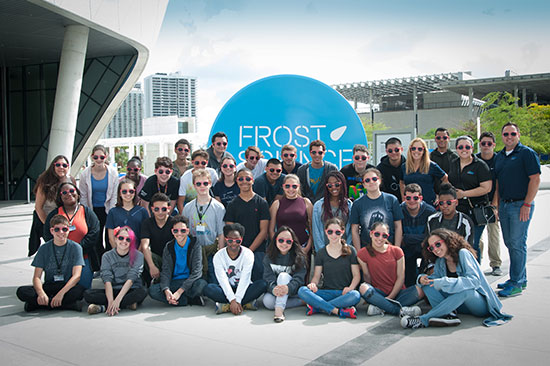 A class of students in bullseye sunglasses in front of the Frost Science Museum sign