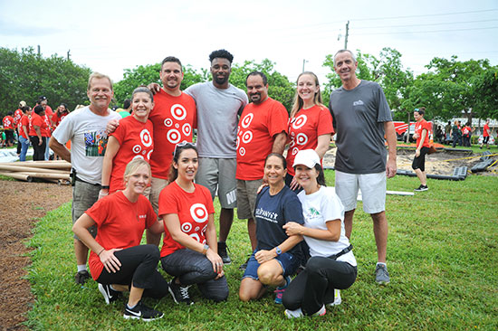 Jarvis Landry stands with 10 volunteers on the grass in the park near the new playgorund