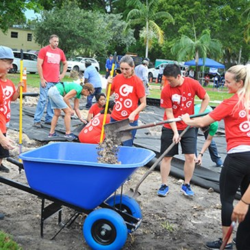 Volunteers shovel mulch into a wheelbarrow