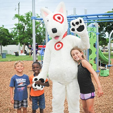 Kids stand on the playground with Bullseye the dog mascot