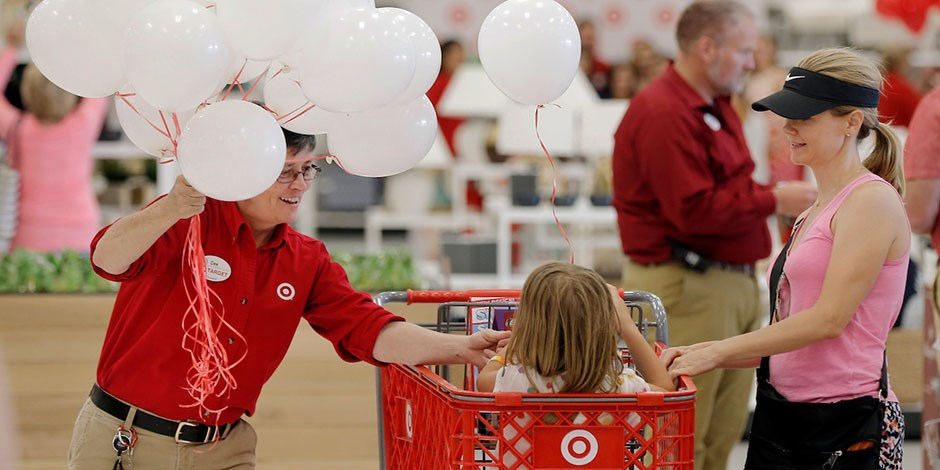 A team member welcomes a guest and a child in a shopping cart with a balloon