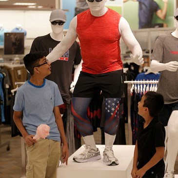 Two kids look up at a living mannequin standing on a platform