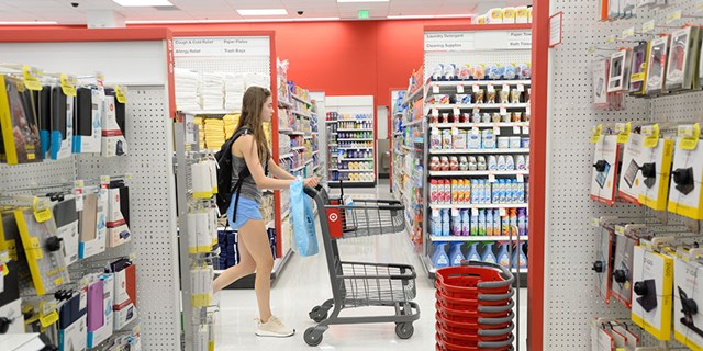 A young woman shops pushing a cart down a Target aisle past shelves full of products