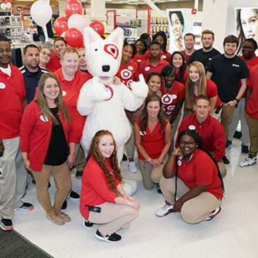 The whole team and Bullseye mascot pose on the sales floor