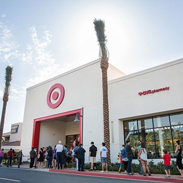 The exterior of the store with palm trees and a line of guests in front