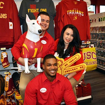 Three team members pose with USC fan gear and Bullseye statue