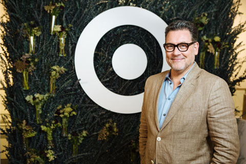 Mark Tritton smiles in front of greenery and a white bullseye