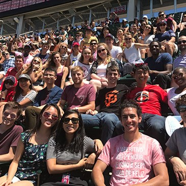A large crowd of interns sitting in the stands at a Twins baseball game