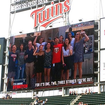 A small group of interns laughs and waves on the big screen at Target Field