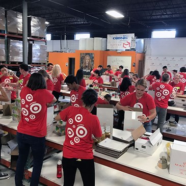 Rows of volunteers in red bullseye shirts pack boxes for a shelter